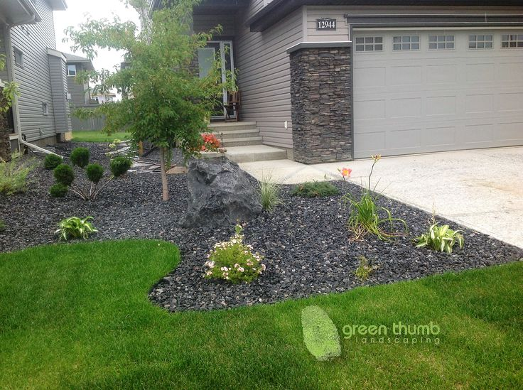 40mm Rundle rock beds with snap edging and an accent boulder. The black Rundle ties in with the colours on the house and brings out the colours in the plants. The snap edging provides an invisible edge.