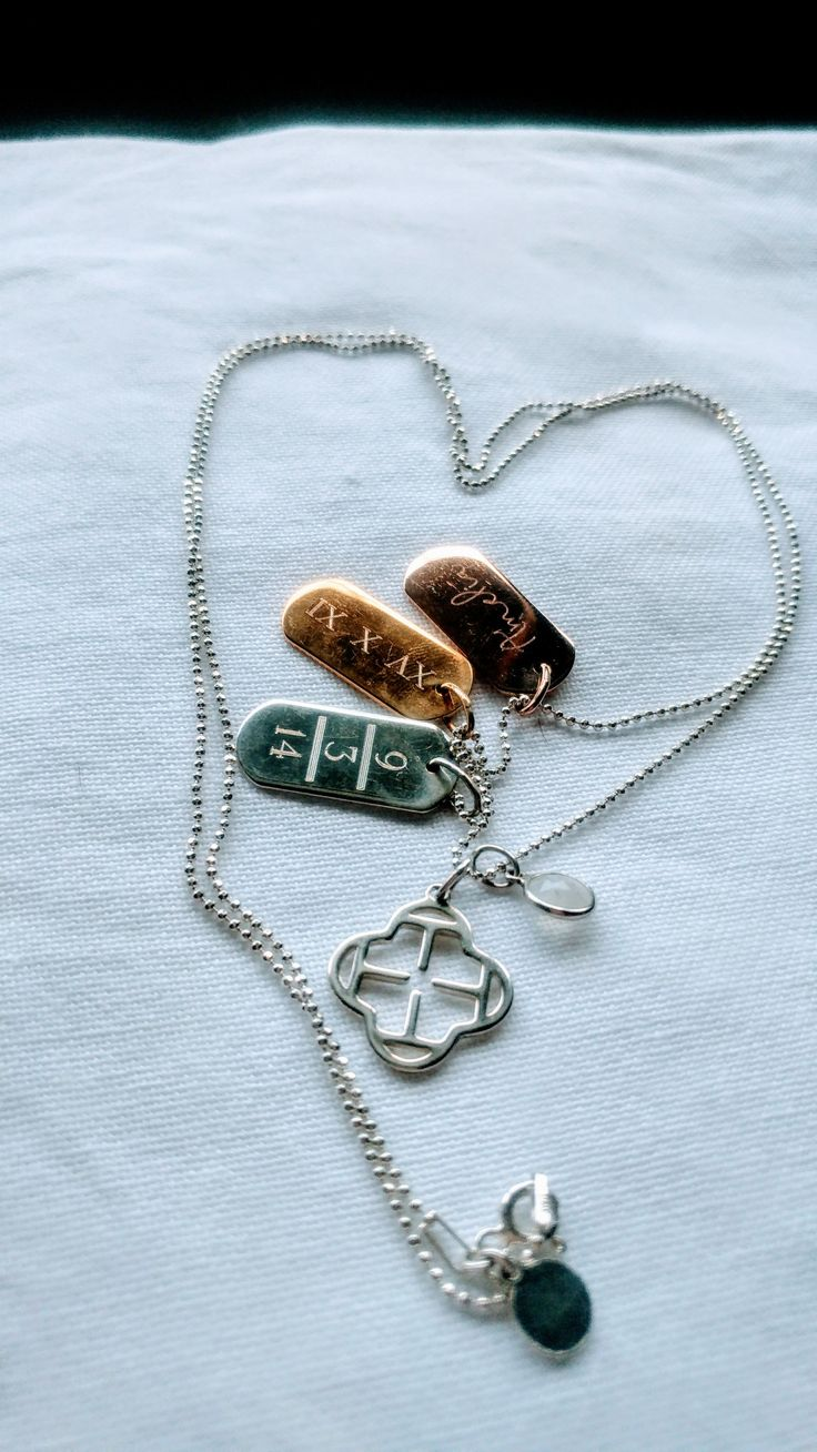 Three signature ID tags engraved with personal messages. My daughter's DOB - silver, my daughter's name - rose gold, my first date with my fiance in Roman numerals - gold! Finished off by adding my birth stone charm and a clover charm of a T for my name.