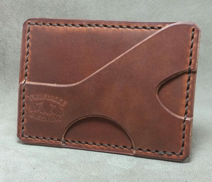 Hand cut and stitched leather minimalist wallet. A minimalist wallet made with quality vegetable tanned leather that features one pocket for I.D. and cards etc.. and a unique cash strap/card holder...