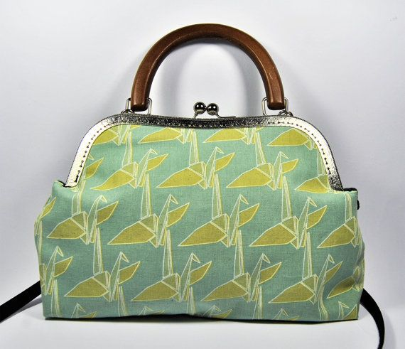 Borsa clutch realizzata in tessuto giapponese verde menta con gru origami. Chiusura a scatto, manico in legno e tracolla removibile.