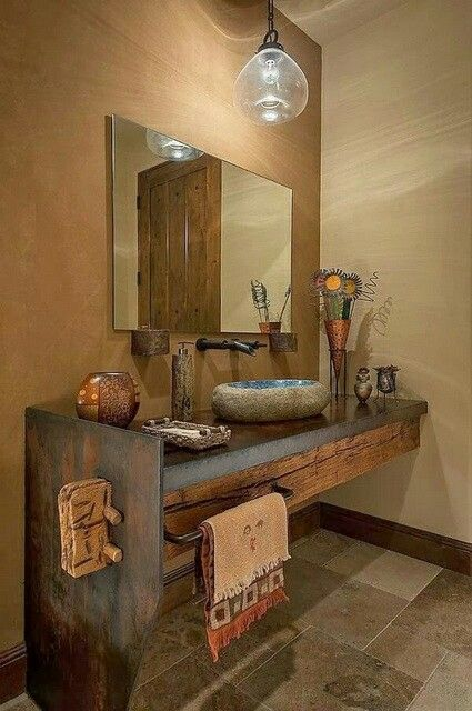 Raw rustic bathroom design, love the raw wood with stone basin, the elements compliment each other, I would have a white wall instead with white towels as well as replacing the metal copper ornament (flowers) with white washed looking stone vase with fresh white lilies inside