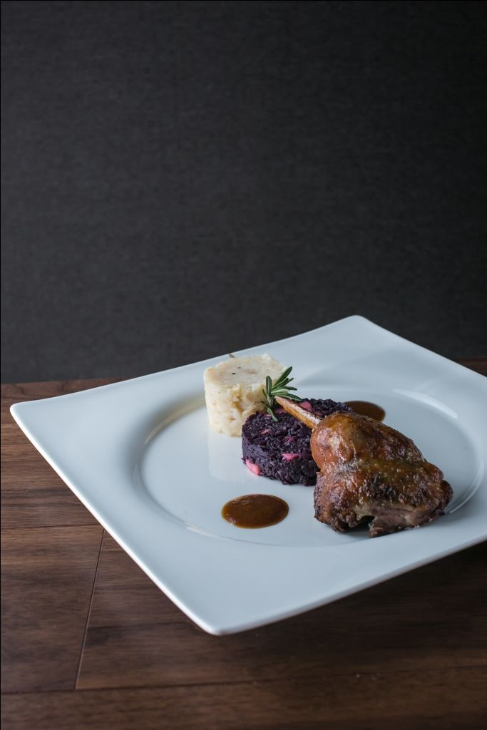 Confited goose drumstick with red cabbage enriched with marzipan and fried apple and with oniony fried potato