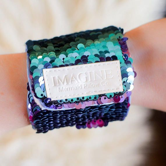 Move over fidget spinners, mermaid bracelets are set to be the newest schoolyard accessory that can provide some sensory distraction for kids who need it, and they are way less annoying. - Red Tricycle  - Adjustable velcro closure; fits ages 4-12+ - Hoda Kotb wore it on the Today Show! (photos below) - Aqua and purple sequins are reversible. When you run your hands over the sequins they flip to a different color. - Features our exclusive Positivity Patch - a daily positive reminder! - Lined…