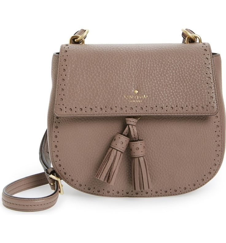 Brogue trim and dual tassels amplify the vintage sophistication of this pebbled leather shoulder bag by Kate Spade in a gracefully curved, structured silhouette.