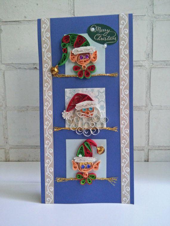 Mignon coloré piquants carte de Noël, qui sera parfait pour l'envoi de vœux de Noël.  La carte est ornée d'un père et deux souriant aides elf. En outre, il est orné de grelots dorés.  Détails : Format - 21 x 10,5 cm / 8,3 x 3,9 (carte pliée). La base de la carte est faite de papier cartonné bleu marine (densité - 280 g / m2). Vide à lintérieur de votre propre message personnel. Livré avec enveloppe.  Frais de port : Expédié sous 1-3 jours ouvrables après confirmation de paiement. Si…