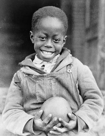 +~+~ Vintage Photograph ~+~+  African American boy holding a piece of fruit received through the Red Cross drought relief work, Mississippi, ca. 1930. Lewis Hine.