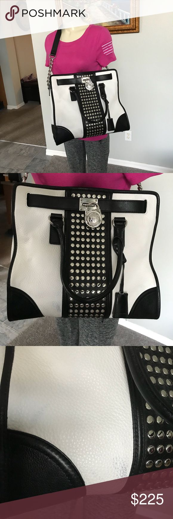 "Michael Kors Hamilton NS Studded Tote MICHAEL Michael Kors Hamilton Center-Stripe Studded Tote STYLE #30T4SHET3L Black/white leather with studded center stripe. Top handles with rings, 5"" drop. Chain shoulder strap. Frame top with logo-engraved lock; magnetic snap closure. Hanging luggage tag with suspended key. Inside, one zip pocket and two open pockets. 14""H x 13""W x 6 1/4""D. Gently Pre Owned Condition, Interior is in great condition, Leather is Soft.. Has a smudge on the left hand side…"