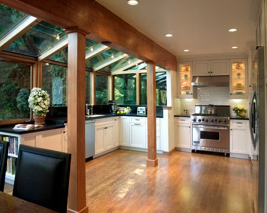 Modern Conservatories for Sunroom and Kitchen: Adorable Traditional Conservatory Kitchen With Brown Laminate Floor Also Wooden Pillars Material Also White Wooden Kitchen Table And Kitchen Cabinets And Drawers Also Stainless Cooker And Modern Ceiling Lights ~ kitchentablecomics.com Others Inspiration