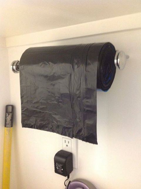 Use a paper towel holder to store trash bags. Get rid of those big ugly boxes.