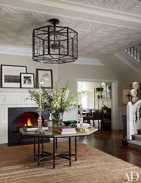 Net-a-Porter founder Natalie Massenet's London entrance hall was decorated by Michael S. Smith and is centered on two strong octagonal elements: a metal ceiling fixture and a vintage Karl Springer table from Liz O'Brien that stands on a Kravet carpet. The house's original 1880s fireplace makes for a warm welcome, while the contemporary works of art propped on its mantel add a casual air.