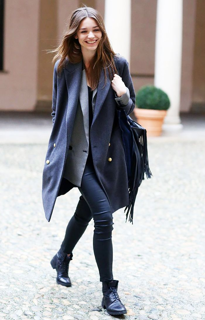 An oversized coat is worn over a blazer and T-shirt and paired with a scarf.
