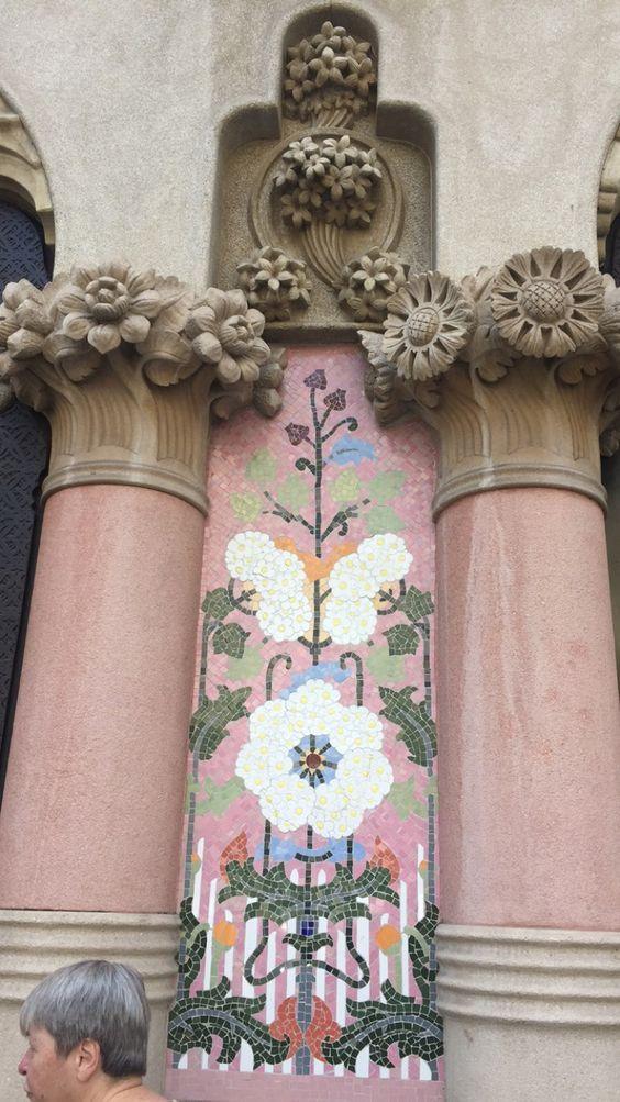 Esta foto es tomada del exterior de la Casa Lleó Morera por el arquitecto Lluís Domènech i Montaner. Esta sección de Trencadis es un buen pop de color que añade detalle a la fachada de un color bronceado. Muchos edificios de Gaudí tienen partes de azulejo en la parte superior del edificio y este arquitecto se distingue por poner el azulejo en la parte inferior a nivel de los ojos. Aunque este edificio no es tan famoso como un monumento grande, representa como largo el movimiento modernisme…