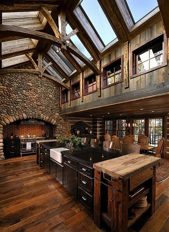 Dark wood and stone hearth surround give this vaulted ceiling kitchen a rustic look, with massive black island bookended by natural wood tables at center.