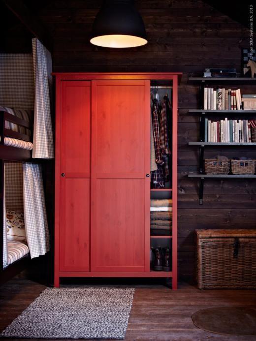 Röda HEMNES garderoben med skjutdörrar gör plats för både kläder och påslakan.