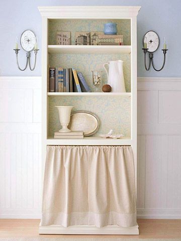 With a pretty damask print in the background and a sassy skirt, this bookcase is given a cottage chic makeover with a feminine flair. To get this look, start by painting the case and shelves cream. Cover the back with a piece of wallpaper in a floral, toile, or damask pattern. Just remember to keep the pattern simple so it doesn't take away from the items you are showcasing in the bookcase.