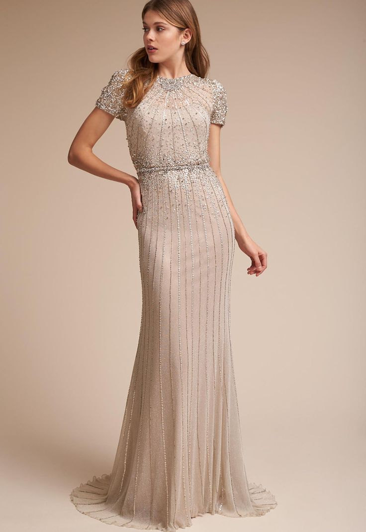 This glamorous column dress steals the spotlight with sequin-encrusted cap sleeves and a bodice featuring deco-inspired sunburst details that go straight to the floor.