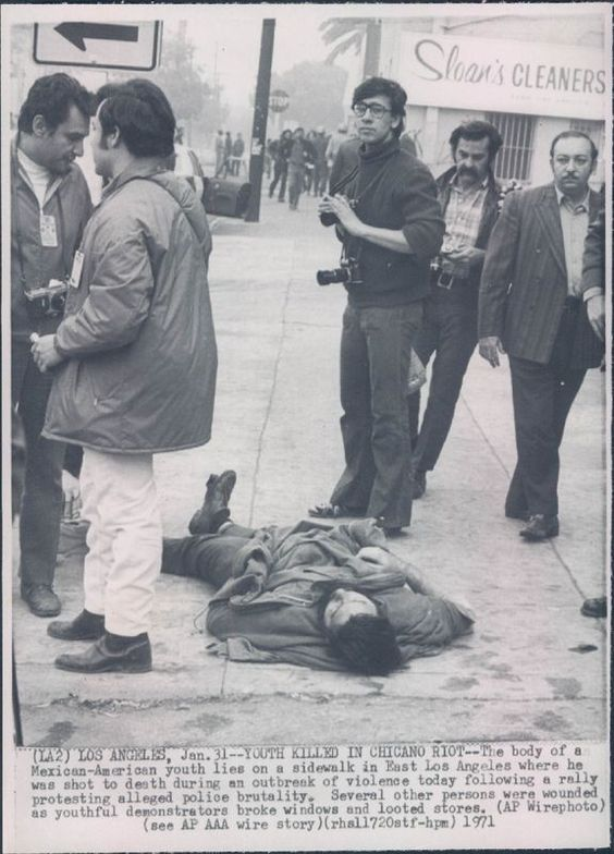"""""""Youth Killed in Chicano Riot--The body of a Mexican-American youth lies on a sidewalk in East Los Angeles where he was shot to death during an outbreak of violence today following a rally protesting alleged police brutality. Several other persons were wounded as youthful demonstrators broke windows and looted stores,"""" January 31, 1971.  Photo credit: AP  Chief Ed Davis of the Los Angeles Police Department blamed the protest on """"swimming pool Communists"""" and the Brown Berets, who he claimed…"""