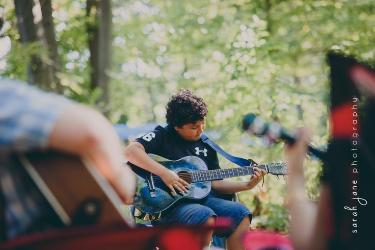 Boy playing his guitar