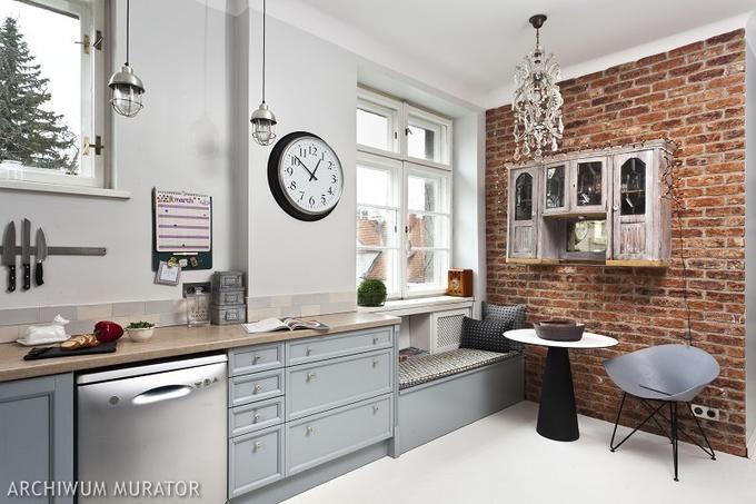 Szare szafki kuchenne na ścianie z czerwonej cegły