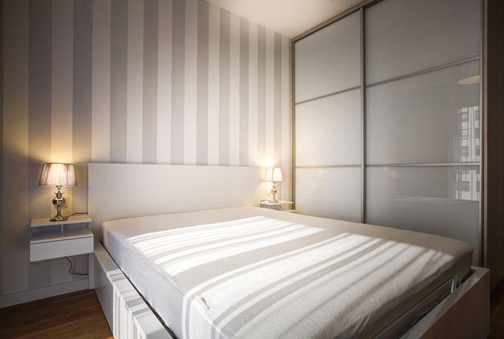 Tapeta w grube pasy w neutralnych kolorach, tworzy przytulny klimat w sypialni.