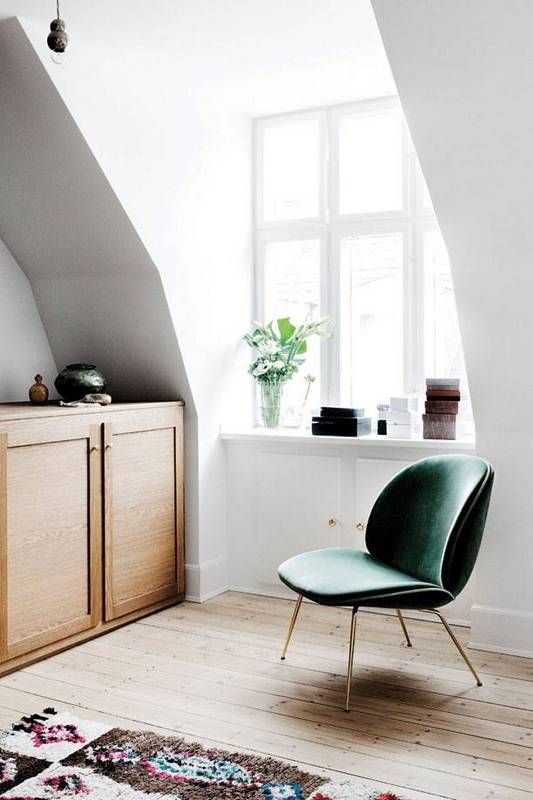 danish interior design white nook with green velvet chair