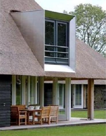 Een hele strakke dakkapel in een rieten dak. De dakkapel heeft openslaande deuren als een Frans balkon.