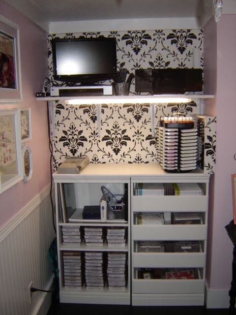 Here is my stamp, ink and cutting area.  I have a shelf on top that is my media area, with a tv, dvr and ipod docking player.  The storage units for my stamps are 2 closet units I got at Menards.  One is just shelves and it holds all my wood mount stamps and my cutters.  The other is a 4-drawer unit and it holds my cling mount stamps.  The tops make a perfect cutting station and I have my ink pad storage units there. I wallpapered the back wall to match some other areas in the room.