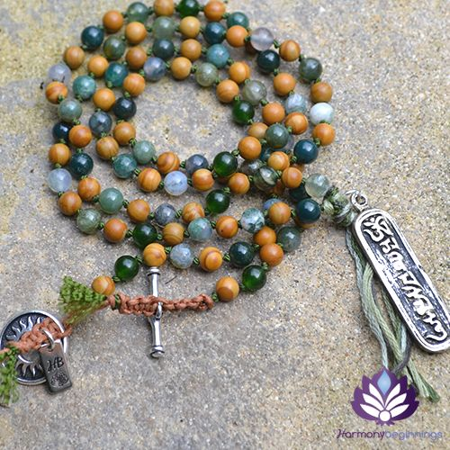 "Our Prayer Necklace has been designed with Moss Agate and wood-laced Gemstones, carrying the hand-carved Mantra ""Om Mani Padme Hum"" amulet. 108 prayer gemstone beads to invoke the sacred power of this mantra. Promoting strength and inspiration for new beginnings. Feel grounded and focused, these Gemstones will aid you with concentration and persistence to clear obstacles, and allow you to see all that is possible.  Finished with a unique hand ..."