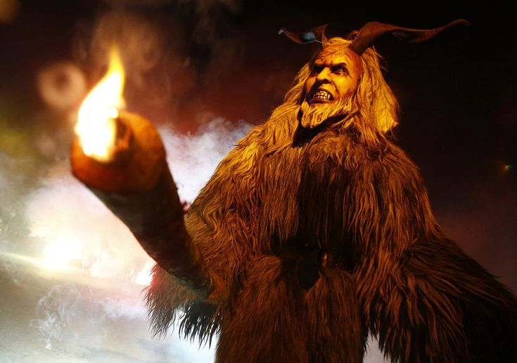 A man dressed in traditional Perchten (also known in some regions as Krampus or Tuifl) costume and mask performs during a Perchten festival ...