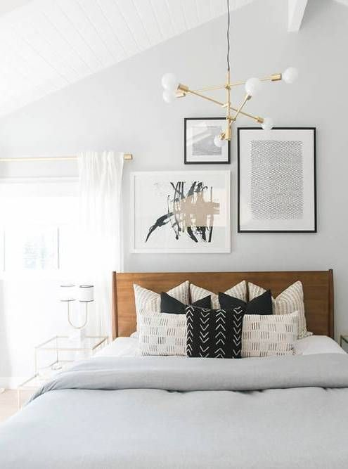 Modern guest room decor with brass light fixture and wooden headboard