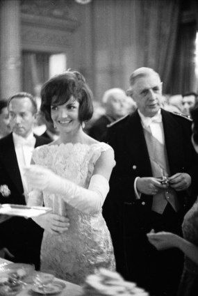 U.S. First Lady Jackie Kennedy attends a luncheon with French President Charles DeGaulle (right)