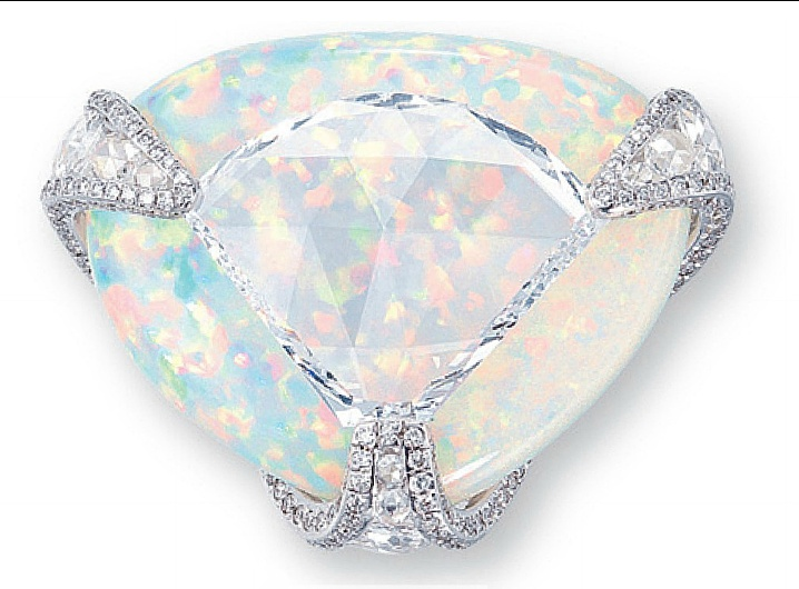 A DIAMOND AND WHITE OPAL RING   Centering upon a shield-shaped rose-cut diamond weighing approximately 5.36 carats, overlapping a triangular-shaped white opal, joined by circular and oval-shaped rose-cut diamond openwork prongs with brilliant-cut diamond trim, mounted in 18k white gol