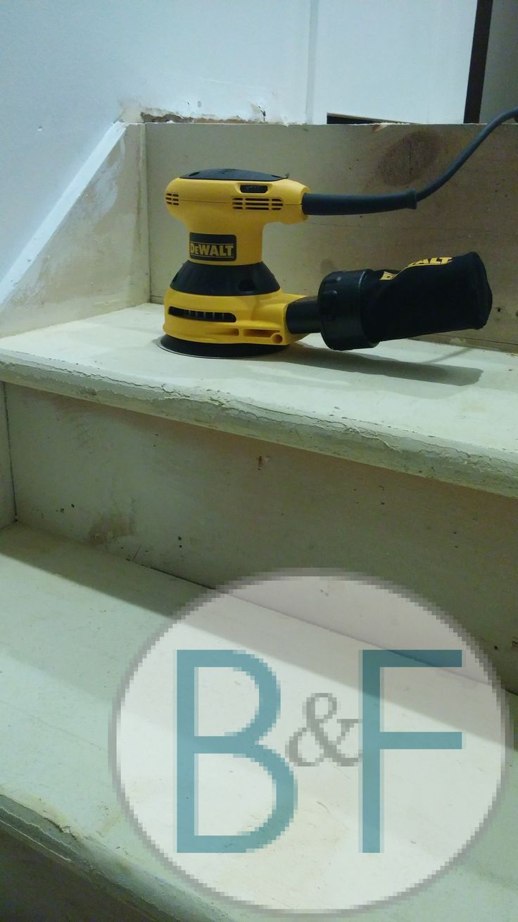 Sanding top of the stairs with electric hand sander