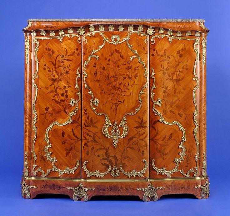 Dreitüriger Louis XV-Bibliotheksschrank Paris um 1745 Allseitig bewegter Korpus mit allseitiger, feiner Blumen- und Blattwerkmarketerie. Vergoldete Bronzeapplikationen. Passige, profilierte Marmorplatte