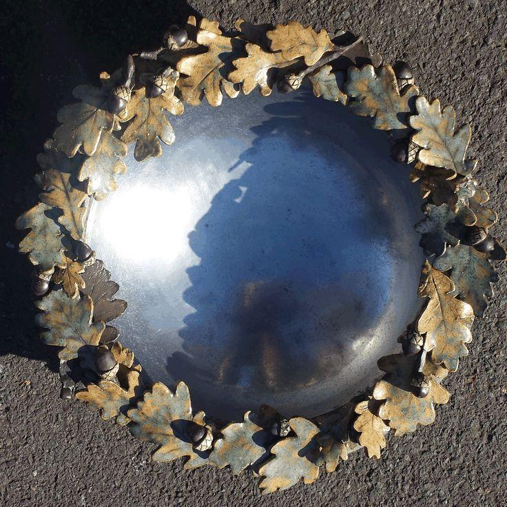 Ceramic oak leaf and acorn wreath adorn a metal bowl.