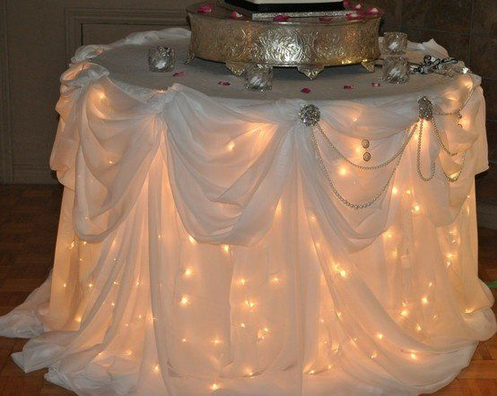 Lights under reception tables. I attended a wedding where they decorated the recieving table with white twinkle lights with a white sheer table cloth draped over and cut glass table topper! Creates a romantic elegant look! | followpics.co