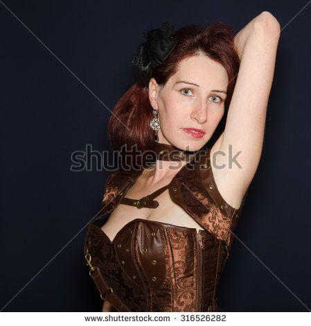 Studio portrait of beauty steam punk girl isolated on black background. #Steampunk #Girl #Portrait #Corset #Fashion #Model #Beauty #Cosmetic #BlueEyes #Vogue #Female #Victorian #Dress