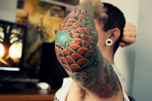 """Spider webs are a popular component of full sleeve tattoos, and this guy's arm tat features a black, yellow and red spider web on the elbow, with a large blue and yellow star at the center. A spider web tattoo on the elbow is actually an old school symbol of a person """"doing ..."""
