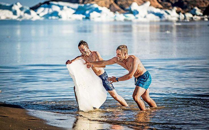 Οι τουρίστες παίζουν με τον πάγο στα κρύα νερά της ανατολικής Γροιλανδίας στο Ammassalik (Tasiilaq).