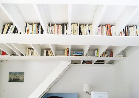 We were charmed to the core over this ingenious book storage idea.  Yes, these are just planks of painted plywood nailed to the supports for the loft above.  They create perfect cubby spaces to store books, baskets and even small lights.