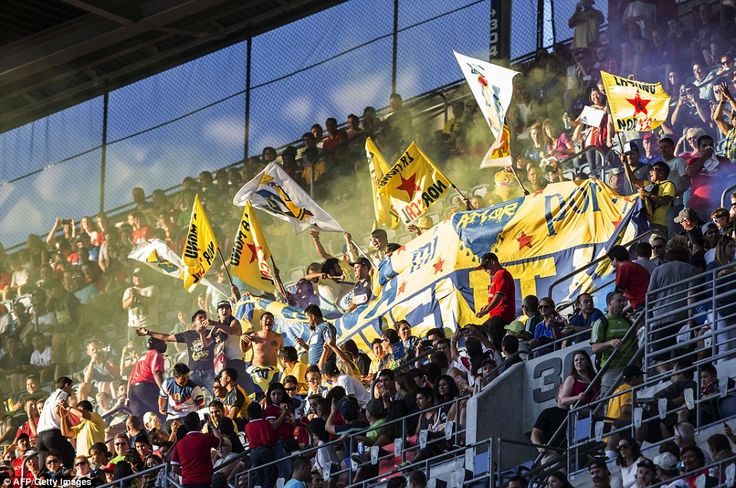 Club America supporters high up in the stands at CenturyLink Field light smoke flares and make themselves heard during the game