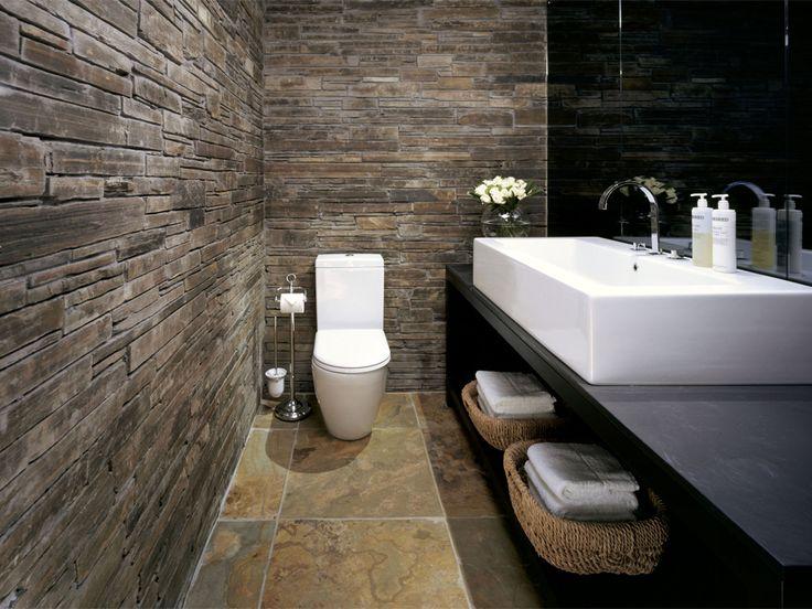 fantastisch toilet, contrast ruwe muur, glad keramiek.