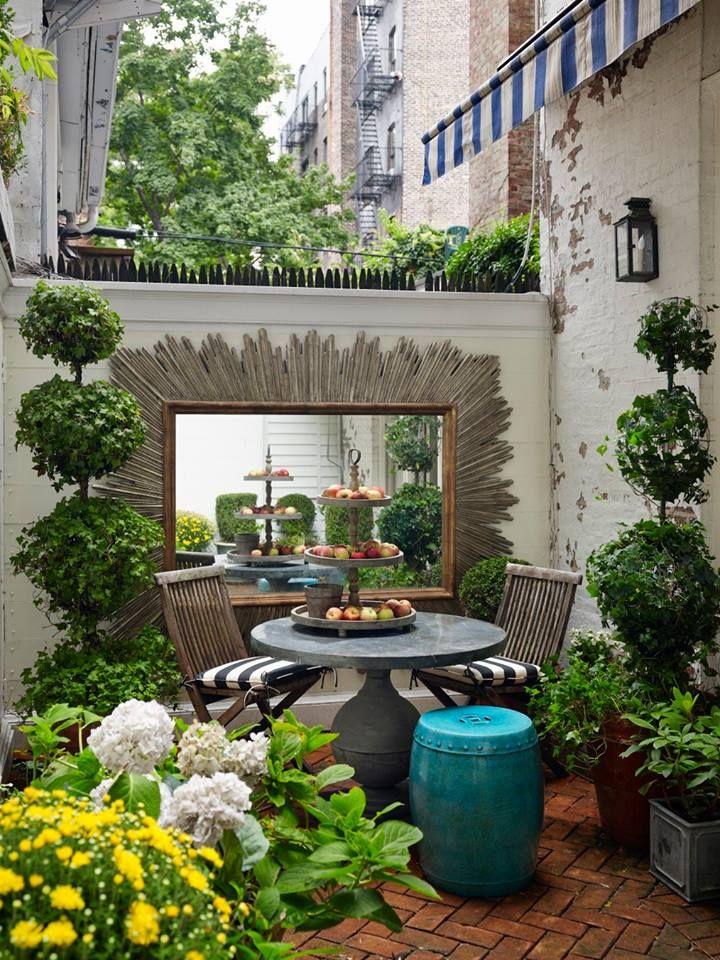 Framed mirror enlarges a cozy outdoor patio space.