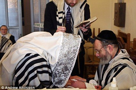 Controversial: A mohel, left, prepares to carry out a circumcision on a baby boy as prayers are read during a traditional Jewish ceremony (file picture)