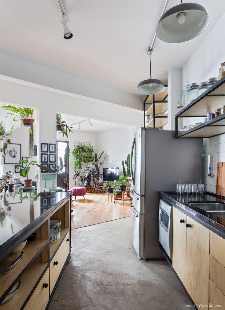 cozinha integrada de estilo industrial com piso de cimento queimado e azulejos de metrô