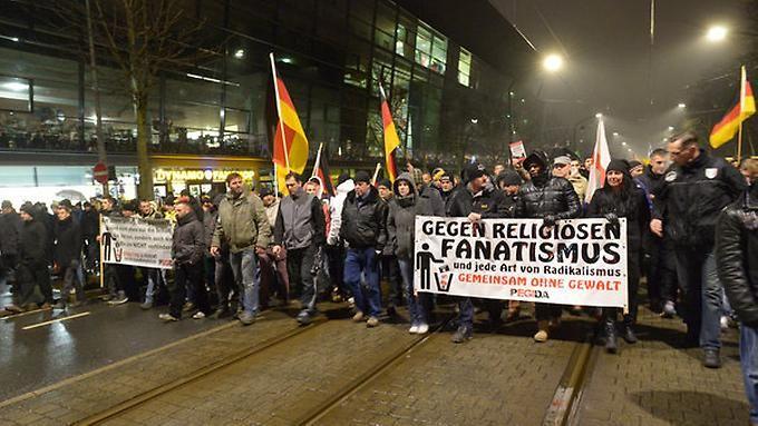 Pegida-Demonstranten ziehen in Dresden am Stadion des Drittligisten Dynamo vorbei.