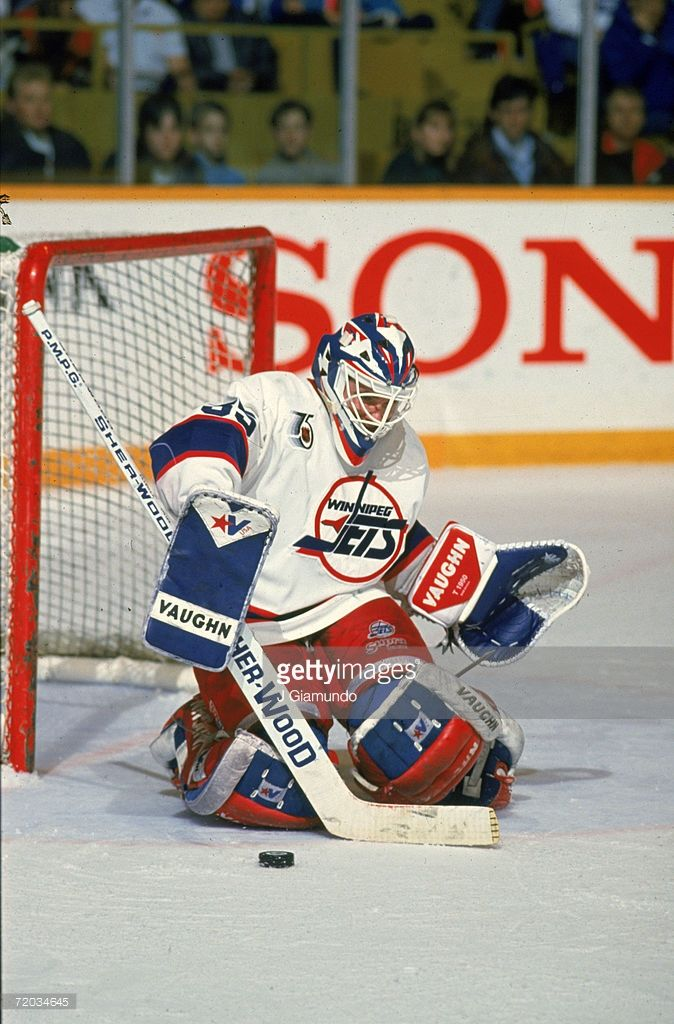 Canadian professional hockey player Bob Essensa, goaltender for the Winnipeg Jets, kneels in front of the goal post as he blocks a puck with his stick during a game with the Toronto Maple Leafs at the Maple Leaf Gardens, Toronto, Ontario, Canada, December 1991