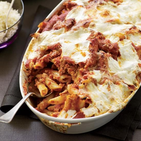 Baked Penne with Sausage and Creamy Ricotta | This hearty pasta dish is studded with chunks of Italian sausage and mixed with a quick garlic-infused tomato sauce. It's then topped with dollops of fresh ricotta and a sprinkling of both mozzarella and Parmigiano-Reggiano, which form a cheesy layer as the pasta bakes.