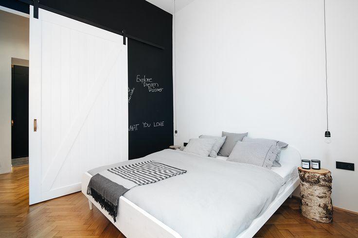 Bíle lakované dřevěné dveře jsou vyrobené na míru, pojíždějí na industriální kolejnici a ložnici oddělují od chodby. Na tabuli si majitelé a jejich hosté nechávají vzkazy - ProŽeny.cz