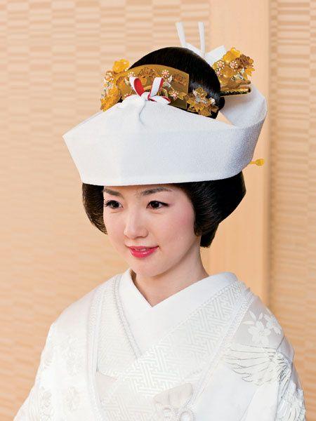 「角隠し(文金高島田)」。角隠し(つのかくし)は、和式の婚礼の儀において、花嫁が文金高島田(ぶんきんたかしまだ)と呼ばれる、日本的な高い髷(まげ)を結った髪の上に、頭を覆う形で被る帯状・幅広の布を言う。(長方形型の一枚の布を、前ひさしを覆うようにして付け、後ろにまわして髷のところでとめる。)素材は白絹であることが多い。